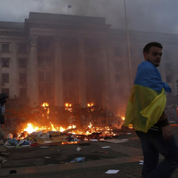 Image: A protester wrapped in a Ukrainian flag walks past a burning tent camp and a fire in the trade union building in Odessa