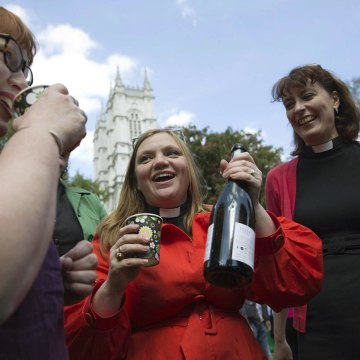 Image: Female priests toast a drink before a march celebrating the 20th anniversary of women becoming ordained priests in the Church of England in London