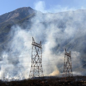Image: Smoke rises near power lines with Cucamonga Peak in the distance at a wildfire in Rancho Cucamonga, California