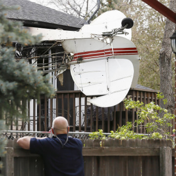 Image: Tim Hanlon looks at the wreckage of a small plane that crashed into a house in Northglenn, Colo.
