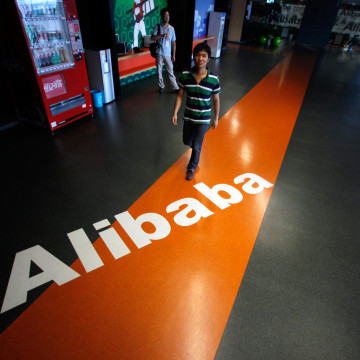 Image: An employee walks past a logo of Alibaba