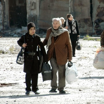 Image: Civilians carry bags during their evacuation from besieged parts of the Syrian city of Homs