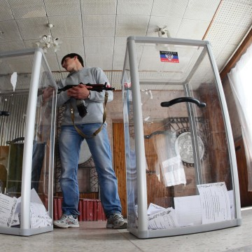 Image: An armed pro-Russian activist stands guard near ballot boxes during the referendum called by pro-Russian rebels