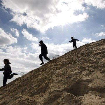 Image: Children play on a large mound of sand on the beach.