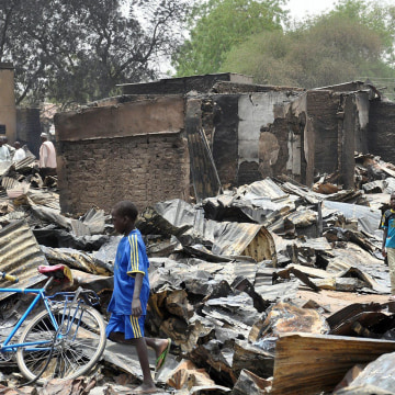 Image: A boy walks past burnt shops at Ngumborum central Market, on May 11