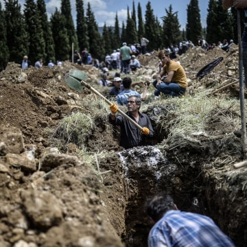 Image: People dig graves for miners killed in the Turkish town of Soma