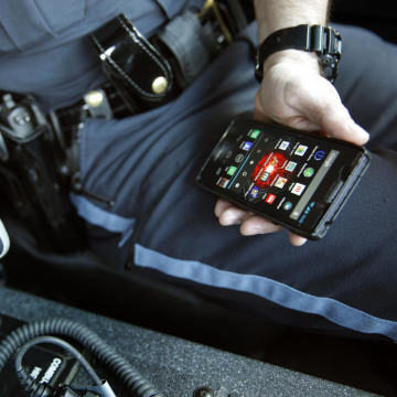 Image: A member of the Kalamazoo Dept. of Public Safety is seen in his armored vehicle holding his cell phone