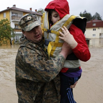 Image: A member of the Bosnian army carries a boy rescued from his home, during floods, in the Bosnian town of Maglaj