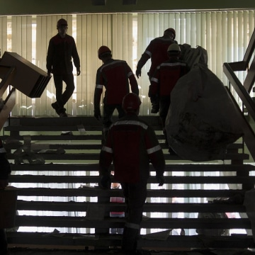 Image: Workers of the Ukrainian company Metinvest clear away debris in a government building in the eastern Ukrainian city of Mariupol, on Frida