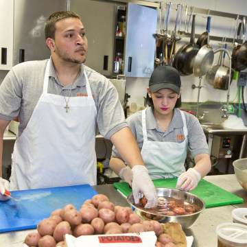 Image: Luis Mateo and Kasandra Vega, both high school dropouts, work in the kitchen of the culinary program of the United Teen Equality Center