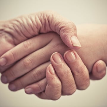 Elderly and younger person shake hands