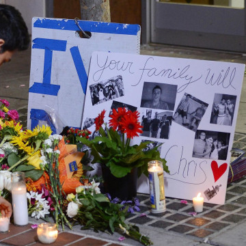 Image: A man places a candle at a makeshift memorial next to the Isla Vista Deli Mart