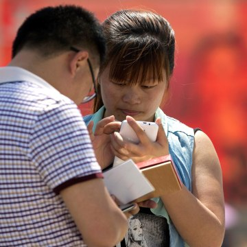 Image: People use smartphones on Tiananmen Square in Beijing
