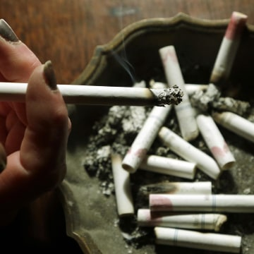 Image: A woman smokes a cigarette at her home in Hayneville, Ala on March 2, 2013