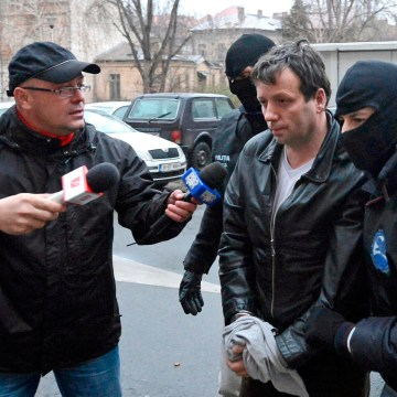 """Image: Lehel, alleged hacker """"Guccifer"""", is escorted by masked policemen in Bucharest, after being arrested in Arad"""