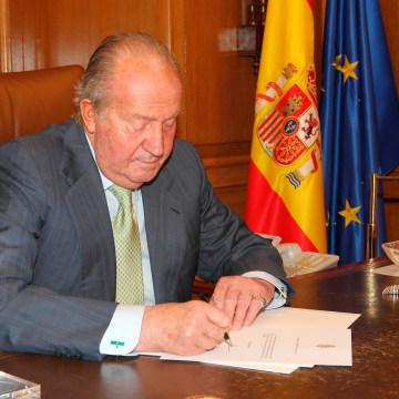 Image: Spain's King Juan Carlos signs his abdication at the Zarzuela Palace