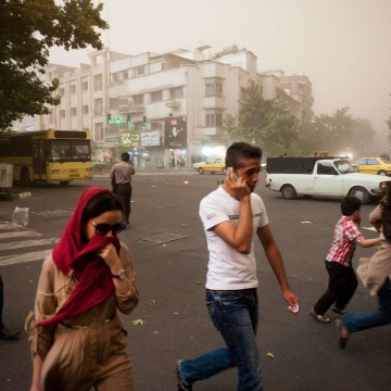 Image: Iranians walk amidst dust as a sandstorm engulfs the capital Tehran on Monday