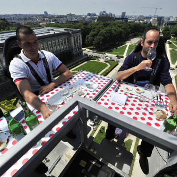 Image: Diners take lunch suspended in the air on Monday above the Parc du Cinquantenaire in Brussels