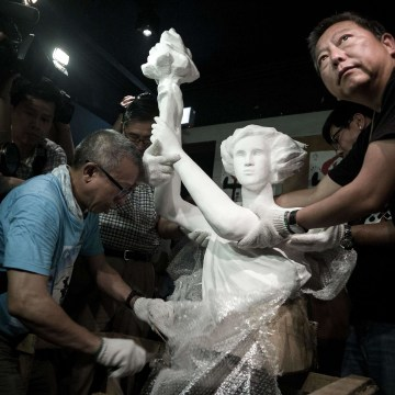 "Image: A ""statue of democracy"" is unpacked by Lee Cheuk-yan, right, at the  June 4 Memorial museum in Hong Kong"