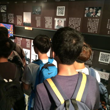 Young Chinese mainlanders crowd around a video at the June 4 museum in Hong Kong.