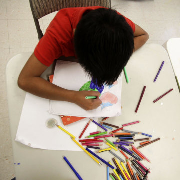 """Image: A boy draws at the shelter for underage immigrants and repatriated minors """"Mexico, my home"""" in Ciudad Juarez"""