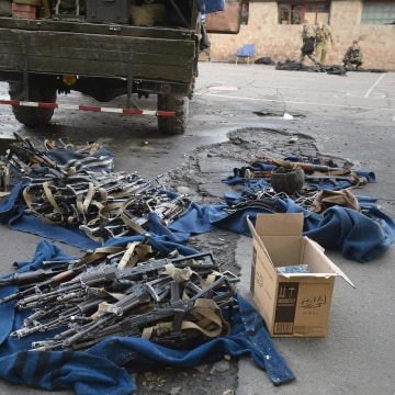 Image: Militants collect weapons and ammunition after they seized a National Guard base in Lugansk