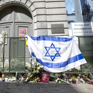 Image: The Belgian and Israeli flag hang on a rail in front of candle and flower tributes a for the victims of a shooting at the Jewish Museum in Brussels, on June 2