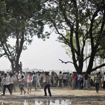 Image: Onlookers stand at site where two teenage girls, who were raped, were hanged from tree at Budaun