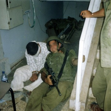 An Israeli soldier poses with a Palestinian detainee in an undated photo taken by a fellow soldier and made available by the campaign group Breaking the Silence.