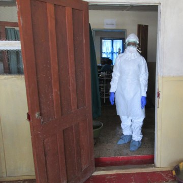 Nurse Veronica Koroma stands in the doorway of the Viral Hemorrhagic Fever (VHF)  ward at Kenema Government Hospital in Sierra Leone.