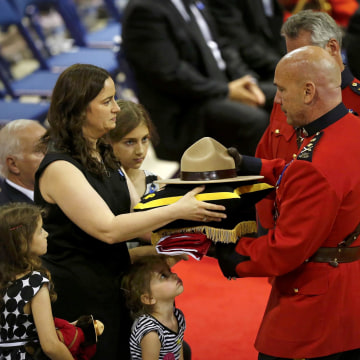 Image: Nadine Larche, the widow of RCMP officer Douglas James Larche, accepts her husband's hat and flag during a regimental funeral for three officers who were killed last week in Moncton