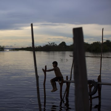 Image: A boy sits on a makeshift dock on the Rio Negro on May 24, 2014, as the sun sets near Manaus, Brazil.