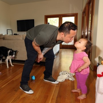 Jet Tila kisses his 19-month old daughter, Amaya, while his wife, Ali, looks on in their Los Angeles home.