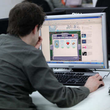 Image: A man sits while working at a computer.