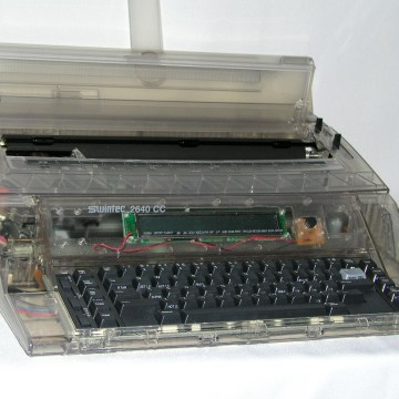 Image: A typewriter made by Swintec with a clear plastic shell.