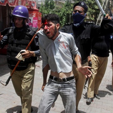 Image: Pakistani policemen arrest an injured protester during clashes