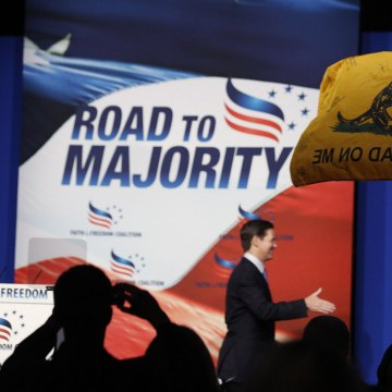 "Image: William Temple, from the Golden Isles Tea Party, waves a flag in the audience at the 5th annual Faith & Freedom Coalition's ""Road to Majority"" Policy Conference in Washington"