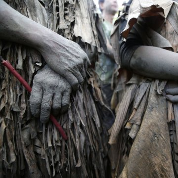 Image: Residents, who are covered in mud and wrapped in dried banana leaves, attend a mass to celebrate the Feast Day of St. John the Baptist at the village of Bibiclat