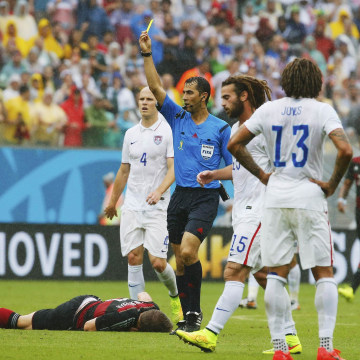 Image: Gonzalez of the U.S. receives a yellow card from referee Irmatov of Uzbekistan for fouling Germany's Schweinsteiger during their 2014 World Cup Group G soccer match at the Pernambuco arena in Recife
