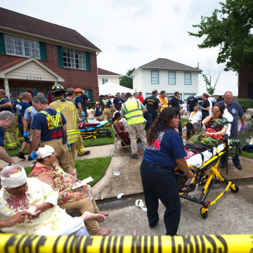 Image: Firefighters and emergency crews treated people outside in a makeshift triage area set up in the front yards of nearby homes after a floor collapsed under a large crowd of people gathered for a religious event in Katy, Texas