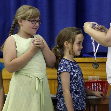 Image:Olivia Drake receives a medal for perfect attendance during an assembly on the final day of school at the Wellington public school in Monticello, Maine.