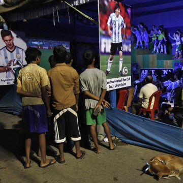 "Image: Indian soccer fans watch 2014 World Cup soccer match between Argentina and Bosnia, on screen installed along roadside inside ""Pandal"" in Kolkata"
