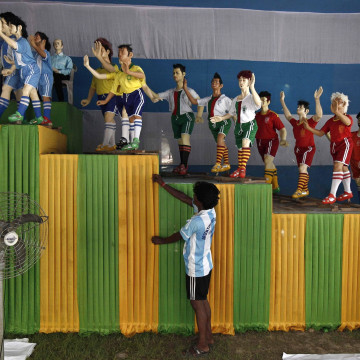 "Image: An Indian soccer fan of Argentina adjusts a cloth in front of clay models of soccer players inside a ""Pandal"" in Kolkata"
