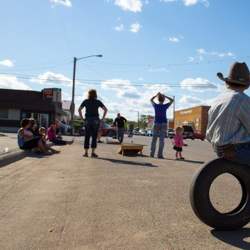 "Image: A young boy takes a break from roping straw bale ""calves"" to watch people toss bean bags during a summer block party on Main Street in Circle, Mont."