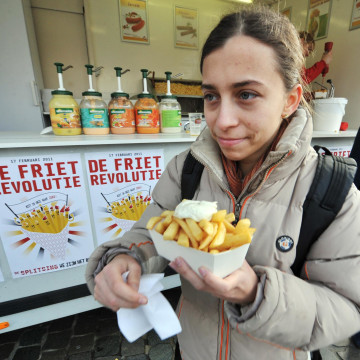 "Image: A woman eats French fries (fried chips) with mayonnaise on the ""Chips Revolution"" Day"" in Leuven"