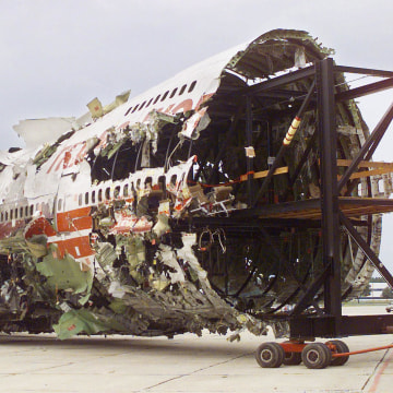 Image: Jim Hall, chairman of the National Transportation Safety Board, looks on as the reconstruction  of TWA Flight 800
