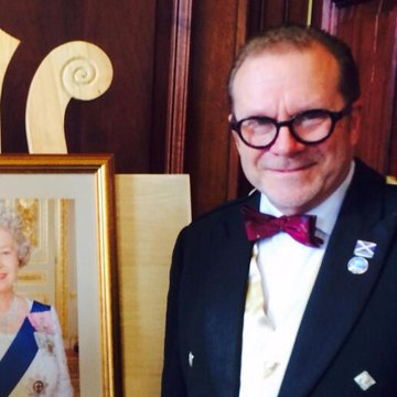 Joe Goldblatt, a Texan who has lived in Scotland for more than a decade, poses next to a portrait of Queen Elizabeth after he gained dual U.S.-British citizenship last month.