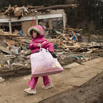 Image: Neena Sasaki, 5, carries some of the family belongings from her home that was destroyed after the devastating earthquake and tsunami on March 15, 2011 in Rikuzentakata, Miyagi province, Japan.