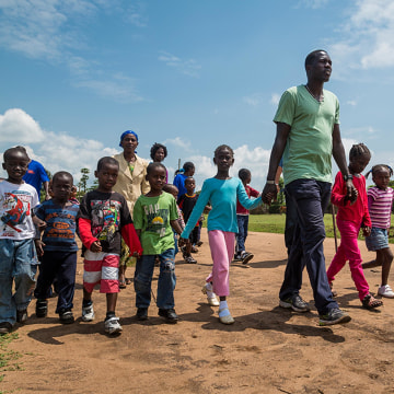 Image: Lale holds hands with children he has helped save.