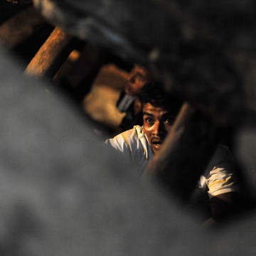 Image: Men make their way inside the collapsed San Juan mine, i
